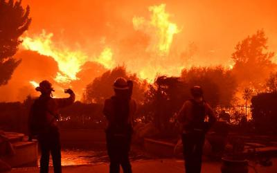 Firefighters look on as a wind-driven wildfire burns Oct. 11, 2019, in Porter Ranch, Calif.