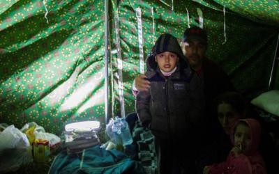 A boy cries inside a tent at a makeshift camp in Thumane, Albania, following a magnitude 6.4 earthquake Nov. 26, 2019.