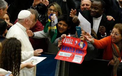 A woman holds a sign next to pope francis