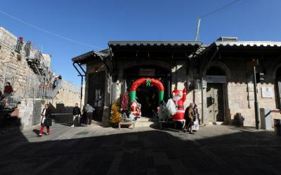 People walk near a Christmas store in Jerusalem's Old City Dec. 18, 2019.