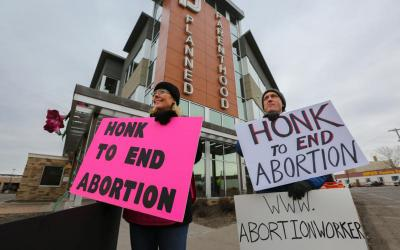 Kalley Yanta and Tom Wooden of Holy Family Catholic Church in St. Louis Park, Minn., demonstrate March 10, 2020, outside a Planned Parenthood building in St. Paul.