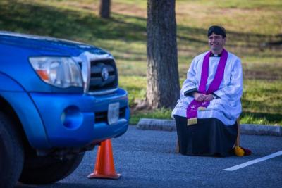 Father Scott Holmer, pastor at St. Edward the Confessor Catholic Church in Bowie, Md., offers drive-through confessions in the parking lot of the parish March 18, 2020.