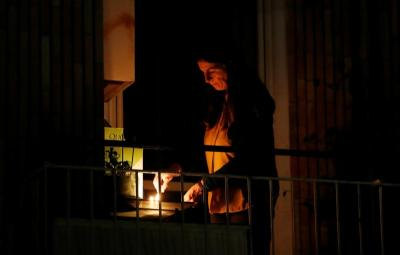 A woman lights a candle on her balcony in Rome March 19, 2020, as faithful across Italy say a prayer for people suffering from COVID-19.