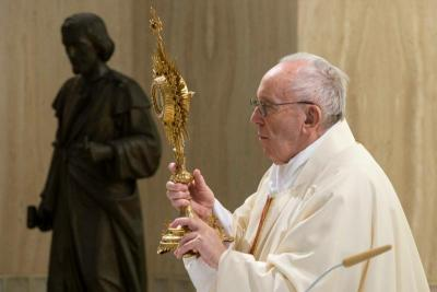 Pope Francis raises a monstrance during eucharistic benediction at the end of Mass May 1, 2020.