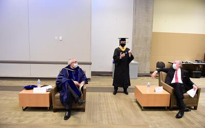 Brendan Dillon, a member of The Catholic University of America class of 2020 and president of the Student Government Association, chats backstage with John Garvey, right, the school's president, and Aaron Dominguez, provost, left, prior to the virtual commencement filming on the Washington campus May 16, 2020.