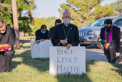 "Bishop Mark J. Seitz of the Diocese of El Paso, Texas, kneels at El Paso's Memorial Park holding a ""Black Lives Matter"" sign June 1, 2020."
