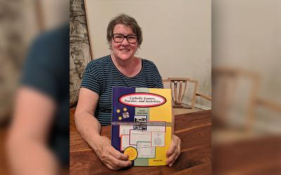Missy Bartlett poses with a Catholic puzzle book in her Louisville, Ky., home, in this June 28, 2020, photo. Bartlett's puzzles are also published in Catholic newspapers across the nation and internationally.
