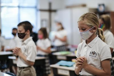 Ashlyn Sellers prays with her fellow fourth-grade students at St. Matthew School in Franklin, Tenn., Aug. 6, 2020, as the new school year begins with extensive COVID-19 protocols in place, including temperature screening and face mask requirements.
