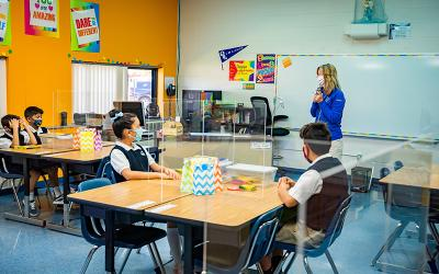 A teacher at Our Lady of the Lakes Elementary School in Waterford, Mich., talks to masked students Aug. 25, 2020, during orientation as the school reopens during the COVID-19 pandemic.