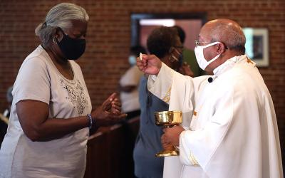 Father Scott Woods, pastor of St. Peter Claver Parish in St. Inigoes, Md., distributes Communion to a woman Sept. 9, 2020, during the Mass to celebrate the feast day of the parish's patron saint and to pray for an end to racism.