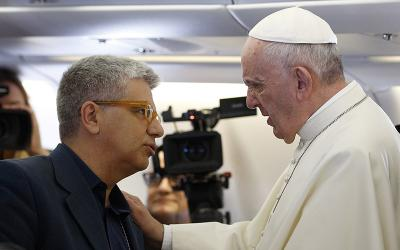 Pope Francis is pictured in a 2015 file photo speaking with Andrea Tornielli, editorial director for the Dicastery for Communication, aboard his flight from Rome to Havana.