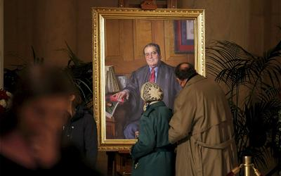 Members of the public pause to look at a portrait of the late Justice Antonin Scalia while his casket lay in repose in the Great Hall of the Supreme Court in Washington Feb. 19, 2016.
