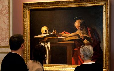 """Visitors are pictured in a file photo looking at a Caravaggio painting titled """"St. Jerome Writing"""" during an exhibition at the Galleria Borghese in Rome."""