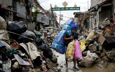 A resident carries his belongings through mud and debris in Manila, Philippines, Nov. 14, 2020, after flooding caused by Typhoon Vamco.