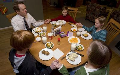 A family prays before dinner at their home in Centreville, Va.