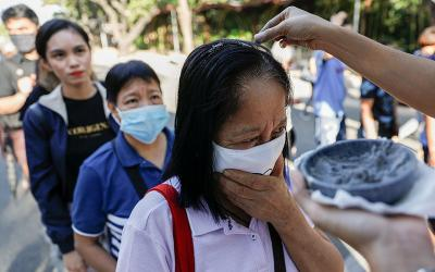 Worshippers wearing protective masks receive ashes during Ash Wednesday Mass at the National Shrine of Our Mother of Perpetual Help in Manila, Philippines, Feb. 26, 2020, during the COVID-19 pandemic.
