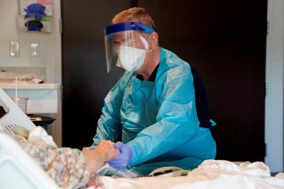 Chaplain Bill Simpson of Shawnee, Okla., prays with a patient undergoing testing for coronavirus at SSM Health St. Anthony Hospital April 23, 2020.