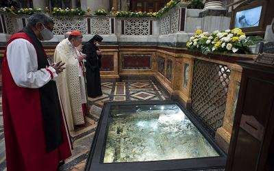 Anglican Archbishop Ian Ernest, director of the Anglican Centre in Rome, Cardinal Kurt Koch, president of the Pontifical Council for Promoting Christian Unity, and Romanian Orthodox Bishop Atanasie Rusnac, vicar for the Diocese of Italy, pray at the tomb of St. Paul during vespers to close the Week of Prayer for Christian Unity, at the Basilica of St. Paul Outside the Walls in Rome Jan. 25, 2021.