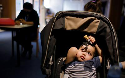 A baby sits in his stroller at La Colaborativa in Chelsea, Mass., March 23, 2021, while his mother fills out paperwork for help with her rent payment.