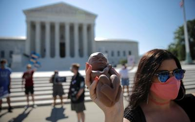 A pro-life activist holds a replica of a fetus outside the U.S. Supreme Court in Washington June 29, 2020.