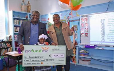 <p>Nazareth Elementary School student Jenesis Shaw and her parents, Micheal and Scotesha, pose with a $1,000 check Jenesis received Nov. 28 from Go Fund Me for her efforts to raise money for children with cancer. (Photo courtesy of Sister Beth Sutter) </p>