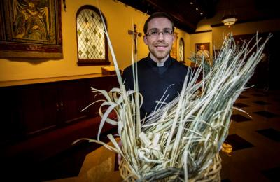 Father John Benson, parochial vicar at the Cathedral of St. Matthew the Apostle in Washington, carries palms in the church sacristy Feb. 18, 2020.