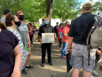 """Father Joshua Laws, pastor of the Catholic Community of South Baltimore, holds a """"Black Lives Matter"""" sign before the start of an interfaith prayer vigil in Baltimore June 3, 2020, to pray for justice and peace following the May 25 death of George Floyd."""