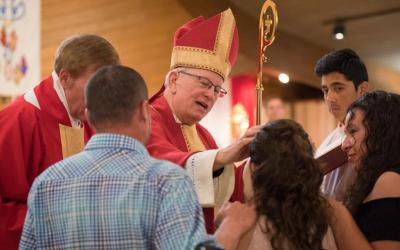 Bishop David L. Ricken of Green Bay, Wis., uses sacred chrism oil to trace a cross on the forehead of Alma Karina Ruiz during the sacrament of confirmation at St. Joseph Church in Wautoma, Wis.
