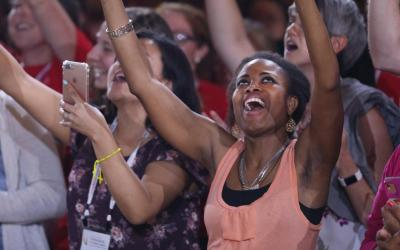 Young people lift their arms in prayer during a convocation in Orlando, Fla.