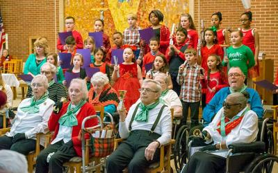 <p>A bell choir from Rochester's St. John Neumann School performs with seniors from St. Ann's home in Rochester Dec. 9. (Photo by Greg Francis)  </p>