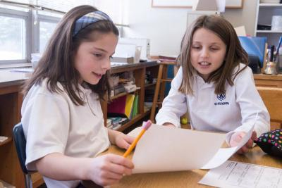 <p>Second-grader Elizabeth Schillaci and fifth-grader Emmy Valentino work together on a project Jan. 30 as part of a buddies program at St. Rita School in Webster. (Courier photo by John Haeger)  </p>