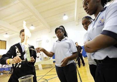 Rochester Academy Charter School freshman Tanaya Wright (center) takes part in a combustion experiment designed by eighth-grader Eleazar Agosto (left) during the school's science fair June 11.