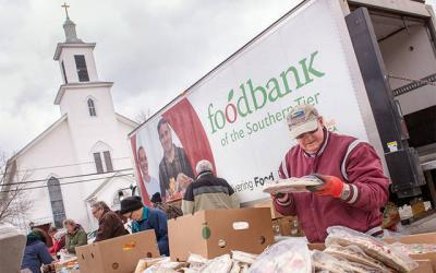 <p>Jim Peters unloads donated food from Food Bank of the Southern Tier in front of St. Joseph Church in Wayland April 11. (Courier photo by Jeff Witherow) </p>