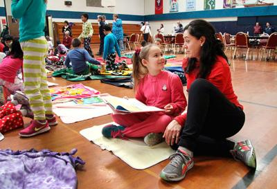 Kindergarten aide Leticia Thomson reads with second-grader Annalise Thompson in the Immaculate Conception School gymnasium Dec. 19. Students brought their pajamas, blankets and favorite books to school to celebrate winning the Diocese of Rochester's Fall Reading Challenge.