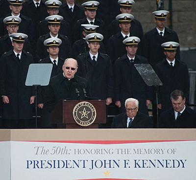 "Bishop Kevin J. Farrell of Dallas delivers the invocation Nov. 22 during the ""The 50th: Honoring the Memory of President John F. Kennedy"" ceremony at Dealey Plaza in Dallas. Behind him is the U.S. Naval Academy Glee Club. Seated to the bishop's left are historian David McCullough and Dallas Mayor Mike Rawlings."