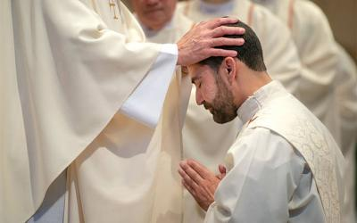 <p>Diocesan priests lay their hands on the head of Father Jeff Chichester during the ordination Mass June 2 at Sacred Heart Cathedral. (Courier photo by Jeff Witherow)  </p>