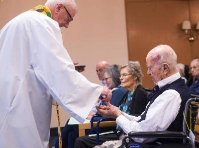 "<p>Father Ed Palumbos presents John ""Jack"" Reinhardt with an award April 3 for his service at Fairport Baptist Homes' weekly Mass. Reinhardt, 95, has served as a lector in the past and currently is the usher and greeter for the liturgies. (Courier photo by John Haeger)  </p>"