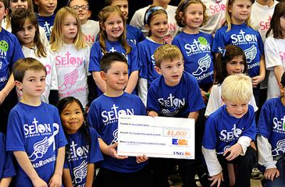 Members of the RoadRunners running club at Seton Catholic School in Brighton gather around a $1,000 check donated by ING Nov. 15.