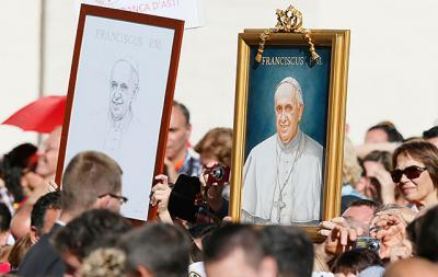 Images of Pope Francis are seen in the crowd during the pontiff's general audience in St. Peter's Square at the Vatican Nov. 6.