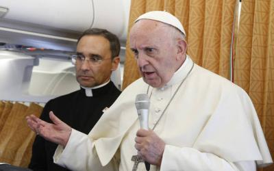 <p>Pope Francis answers questions from journalists aboard his flight from Geneva to Rome June 21. In the background is Father Mauricio Rueda Beltz, papal trip organizer.  </p>