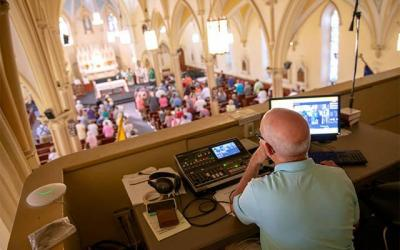 Video operator Mike Paulin looks over the camera feed during a Sept. 15 Mass at Corning's St. Mary Church. (Courier photo by Jeff Witherow)