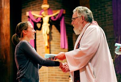 St. Kateri Tekakwitha parishioner Emma Schum accepts her plaque from Father Daniel Condon during a March 6 Hands of Christ recognition ceremony at Fairport's St. John of Rochester Church.