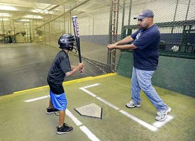 Carlos Torres (right), president of the Rochester Hispanic Youth Baseball League and coach of the league's Padres team, gives some batting advice to Padres player Jorge González during a June 8 practice at the Rochester Sports Garden in Henrietta.