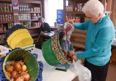 <p>Sister Mary O'Brien, executive director of Tioga County Rural Ministry, fills a basket with potatoes at the ministry's food pantry Nov. 26. The ministry recently celebrated its 40th anniversary.  (Courier photo by John Haeger) </p>