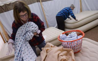 <p>Marge Doyle strips bedding as Eileen Doyle wipes down beds at the Church of the Epiphany's parish center in Sodus Nov. 25. The church is a host congregation for Family Promise of Wayne County, which assists homeless families. (Courier photo by John Haeger) </p>