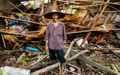 <p>An Indonesian man stands in front of his destroyed house Dec. 24 after a tsunami hit two islands. Indonesian authorities asked people to avoid the coast in areas where the tsunami killed more than 400 people. (CNS photo by Jorge Silva/Reuters)  </p>