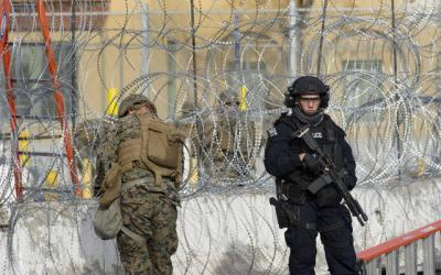 <p>A U.S. Customs and Border Protection officer (right) stands next to a member of the U.S. military working with concertina wire during a show of force and exercise to secure the San Ysidro Port of Entry Nov. 22 in San Diego. The show of force and exercise were in response to the presence of a large caravan of mainly Honduran migrants that recently arrived in neighboring Tijuana, Mexico. (CNS photo by David Maung)  </p>