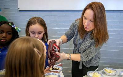 <p>Parent volunteer Kathy Harlacker pours chocolate syrup during a Catholic Schools Week ice cream party at All Saints Academy in Corning Jan. 29.  </p>
