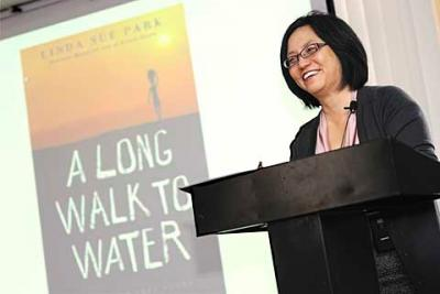 "Rochester author Linda Sue Park discusses her latest book, ""A Long Walk to Water,"" during an appearance at Monroe Community College's Damon City Campus Dec. 6. The book is based on the life of Sudanese refugee Salva Dut, pictured below in a photo by Ken Riemer, courtesy of Water for Sudan."