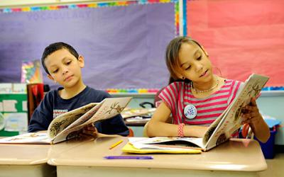 Third-graders Juan Robles (left) and Leyla Robles read the book Pretty Salma June 19 at Rochester's School No. 35.